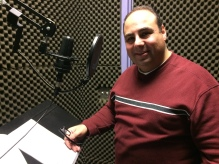 In a sound proof studio recording the narration of the documentary.